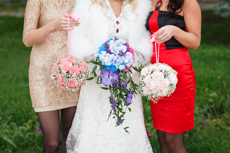 bridesmaids: three young bridesmaids holding wedding bouquets outdoor