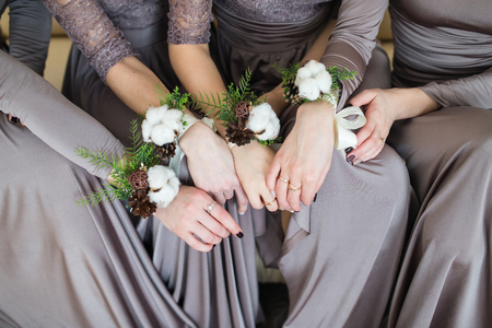 buttonhole: bridesmaids with wedding bouquet of flowers at  bridal ceremony. bridesmaids with boutonniere buttonhole at wedding day. bride friends with marriage flowers wedding. woman with wedding hands flowers Stock Photo