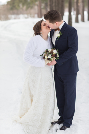 glory of the snow: Young couple newlyweds walking in a winter forest in the snow. Bride and groom hugging in the park in winter. Beautiful man and woman in their wedding clothes are among the pines.
