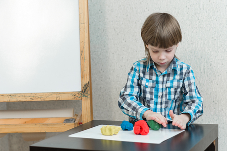 developmental: Blond boy sculpts from plasticine at home at the table. The idea and concept of the school, school, home education and developmental activities.