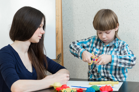 tinkering: Mother and son at home molded from clay and play together. The idea and concept of the school, school, home education and developmental activities. Stock Photo