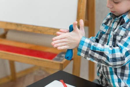 Blond boy sculpts from plasticine at home at the table.