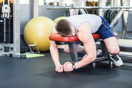 Tired and desperate men at the gym. Male athlete lying on a bench, exhausted. Stock Photo