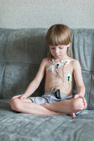 medical exam: Child sitting on the sofa with Heart cardiogram or monitoring of cardiac performance using Holter.