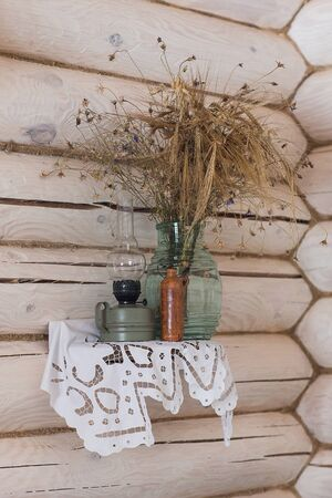 jag: Sill life with Russian clay jag, oil lamp, bird nest, bunch of willows, bouquet of flowers on the linen napkin Stock Photo