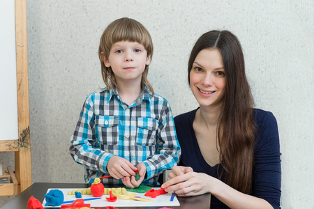 tinkering: Mother and son at home with molded clay and play together. Stock Photo