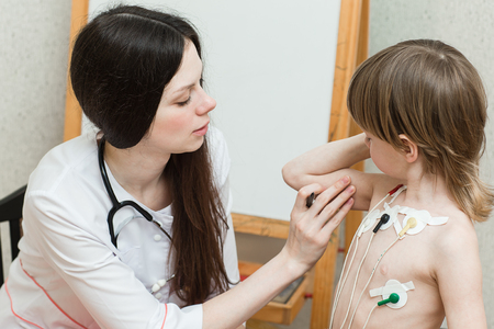 medical exam: Female doctor doing, Cardiogram of heart of the boy, holter