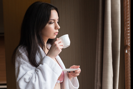 wellness sleepy: Beautiful young woman in lingerie in the apartment holding a cup of coffee in the morning.