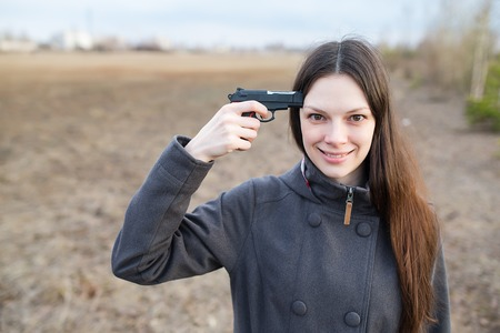 death head holding: Woman with gun want to commit suicide