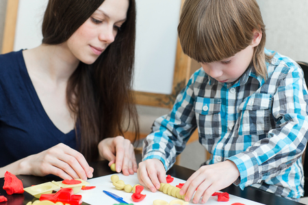 teaching material: Mother and son at home molded from clay and play together.