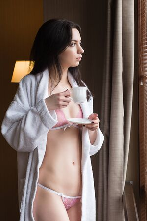 wellness sleepy: Beautiful young woman in sexy lingerie in the apartment holding a cup of coffee in the morning.