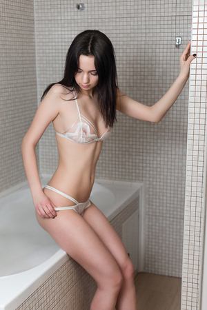 brunette lingerie: Beautiful young woman in sexy lingerie takes a shower in the bathroom in apartments.