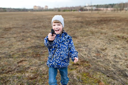 dirt road recreation: Happy and cheerful boy playing with a gun. Stock Photo