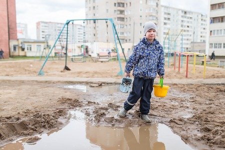 smutty: Boy playing with a shovel and bucket in a muddy puddle.