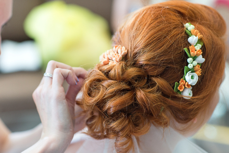The hairdresser does a hairstyle to the bride Stock Photo