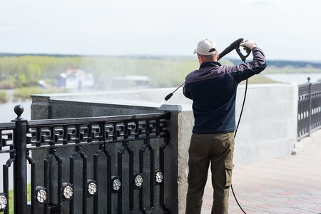 Construction worker cleaning wall with water hose