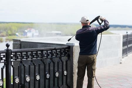 Pracownik budowlany czyści ścianę z wodnym wężem elastycznym