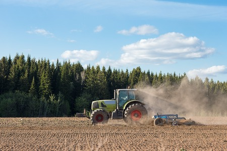 plough machine: Farmer in tractor preparing farmland with seedbed