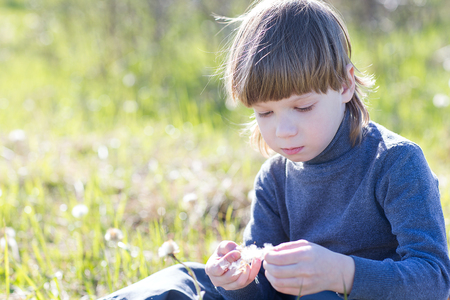 one child: A child sits, thinks and dreaming on grass