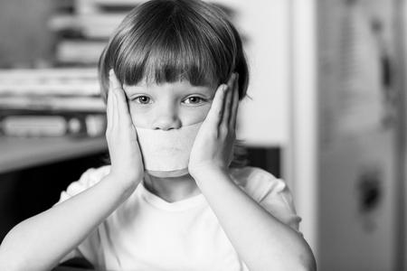 child protection: Offended child sits at a table with his mouth sealed with tape. The concept of domestic violence and child protection.
