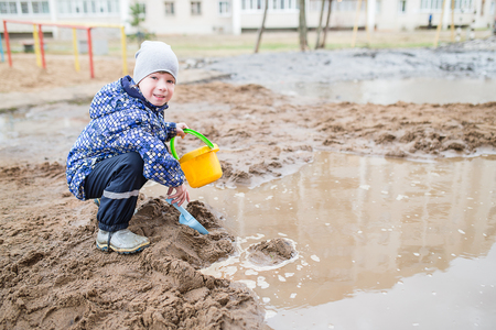 smutty: Boy playing with a shovel and bucket in a muddy puddle. Child building sand in the playground.