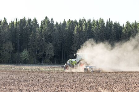 next year: Farmer in tractor preparing farmland with seedbed for the next year