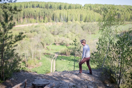 edge of cliff: A man stand on the edge of a cliff and looking to the valley landscape