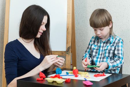 developmental: Mother and son at home molded from clay and play together. The idea and concept of the school, school, home education and developmental activities. Stock Photo