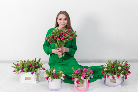 women s health: Beautiful young woman with a bouquet of flowers in a gift box. The idea and concept gift woman birthday, March 8, Valentines Day and other romantic celebrations.