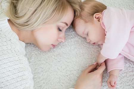 Young beautiful mother puts her baby daughter to sleep. motherhood concept, love and care.