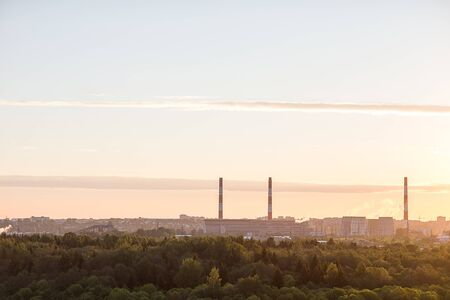 temelin: Tower and chimneys of the plant at dawn on the outskirts of the city in a forest.