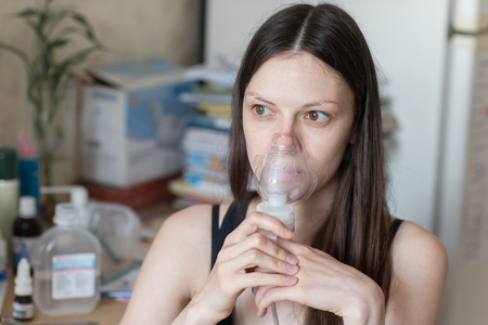 Young girl turning on respiratory inhaler for Asthma Treatment indoor 스톡 콘텐츠