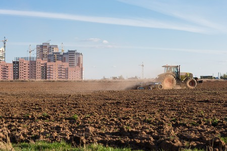 industrialization: The industrialization of the vast expanses. Tractor plowing land on the background of houses under construction. Stock Photo