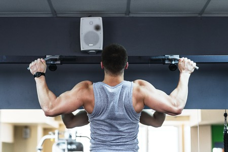 lats: young bodybuilder training in the gym.  The man in the gym is tightened on the bar.