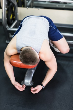 tired person: Tired and desperate men at the gym. Male athlete lying on a bench, exhausted. Stock Photo