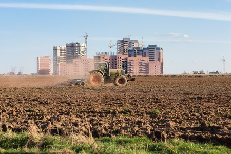 The industrialization of the vast expanses. Tractor plowing land on the background of houses under construction. Standard-Bild