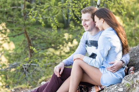 Young couple sitting on the edge of a cliff to cliff and enjoy the view. Freedom, independence and relaxation concept.