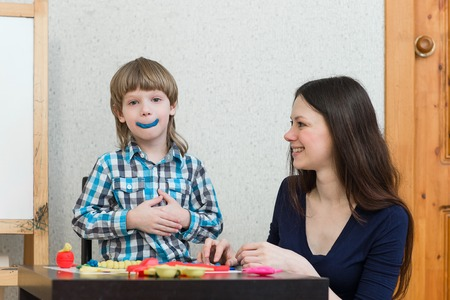 teaching material: Mother and son at home molded from clay and play together. The idea and concept of the school, school, home education and developmental activities. Stock Photo