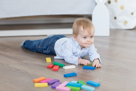 Baby boy twins playing with the toy wooden cubes and dice Stock Photo