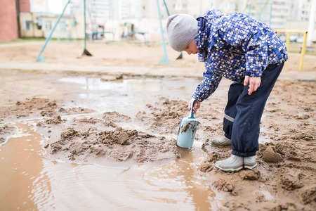 Boy playing with a shovel and bucket in a muddy puddle. Child building sand in the playground.