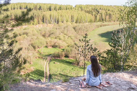 edge of cliff: Young woman hiker sits on the edge of the cliff and enjoying forest in the mountains