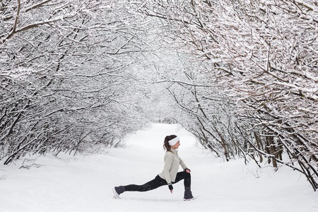 Young woman doing stretching exercises during winter training outside in cold snow weather in park. Trees in the snow. Weather snow cloud. Fitness on the street in the winter.