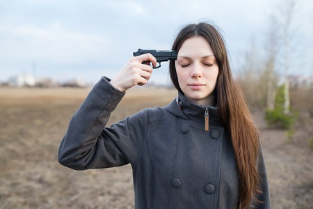 holding gun to head: Woman with gun want to commit suicide