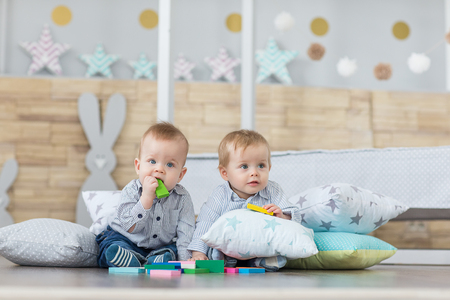 Baby boy twins playing with the toy wooden cubes and dice Standard-Bild