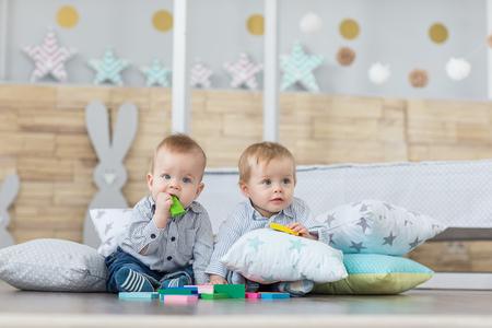 Babyjongen tweeling spelen met de speelgoed houten kubussen en dobbelstenen