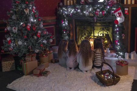 fireplace home: Cute little kids sitting on rug near fireplace at home
