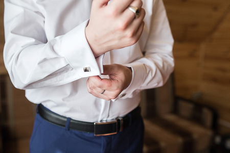 cuff link: close up of a hand man how wears white shirt and cufflink
