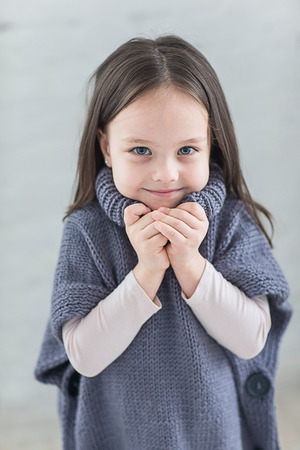 warm jacket: Fashion child knitted sweater in the Studio. The child in a warm jacket. Stock Photo