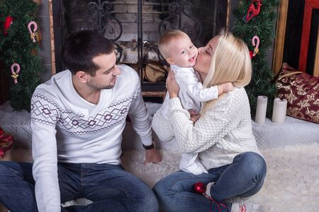 fireplace family: Happy family celebrating Christmas at home by the fireplace and the Christmas tree.