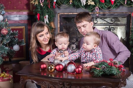 foretaste: Christmas. Young family has a rest. The room is festively decorated. Stock Photo